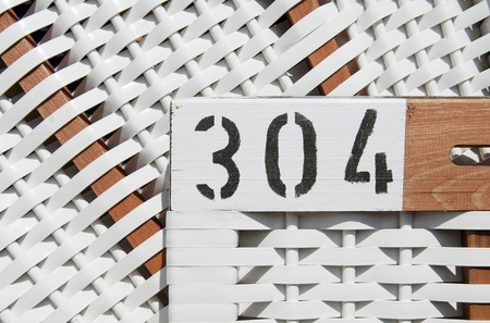 german north sea region: Detail of typical beach chair, the focus is on the number 304, Germany.