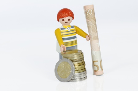 care allowance: Muenster, Germany - April 22, 2011: Playmobil man with euro coins and 50 euro banknote in his hands isolated on white. Playmobil are famous construction toys manufactured by the Brandstaetter Group, headquartered in Zirndorf, Germany.