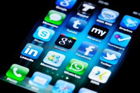 Muenster, Germany - August 25, 2011: A close up of an Apple iPhone 4 screen showing various social media apps, including Skype, Google+, Facebook, Twitter, LinkedIn, Myspace, tumblr, foursquare, and Messenger. Stock Photo - 12147679