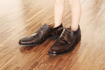 floor standing: Big shoes to fill, child s feet in large brown shoes, on walnut parquet floor
