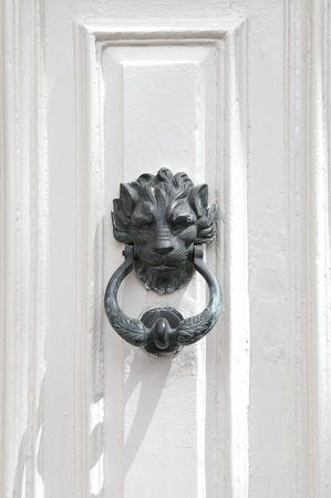 Bronze lion door knocker on white door in Mdina, Malta  photo