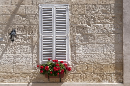 Deterorating window with white shutters in Sliema, Malta  photo