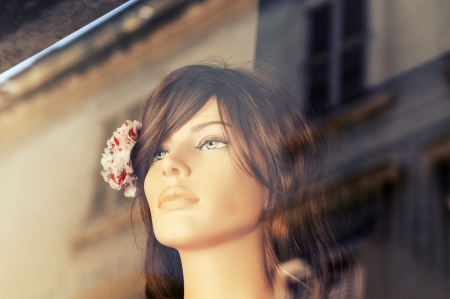 Portrait of female mannequin in store window, toned image  photo