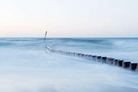 german north sea region: Long exposure of misty sea and wooden breakwater,  north sea region, Germany, toned image. Stock Photo