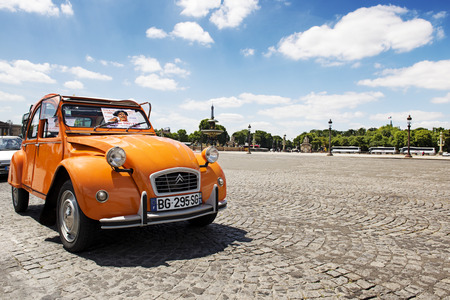 PARIS, FRANCE - JUNE 20, 2014: Old Citroen 2CV parked at Place de la concorde, Paris, France. Antique orange Citroen 2CV is a French produced car, built from 1948 through 1990 with a unconventional look.