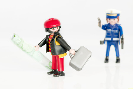 Muenster, Germany - April 22, 2011: A Playmobil policeman chasing a bank robber isolated on white. Playmobil are famous construction toys manufactured by the Brandstaetter Group, headquartered in Zirndorf, Germany.