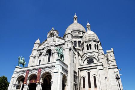 cur: The Basilica of the Sacred Heart of Paris, Sacré-Cœur Basilica, located on Montmartre, the highest point in Paris, France. Stock Photo