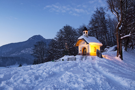Chapel at Lockstein in Berchtesgaden at sunset with Christmas tree in front of mountain, Germany.