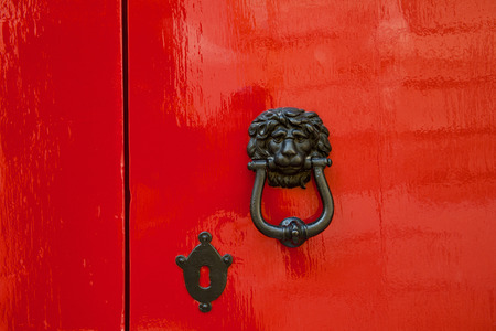 heads old building facade: Old red door with lion head metal knockers, Mdina, Malta. Stock Photo