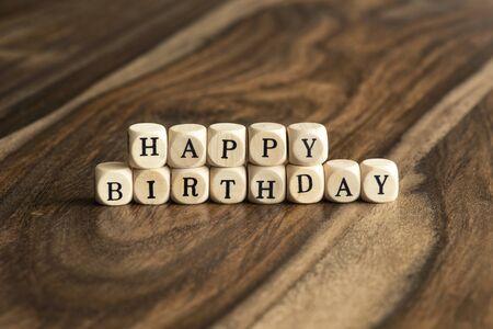 congratulating: HAPPY BIRTHDAY word background on wood blocks