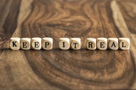 zakelijk: HOUD HET ECHT woord achtergrond op houten blokken Stockfoto