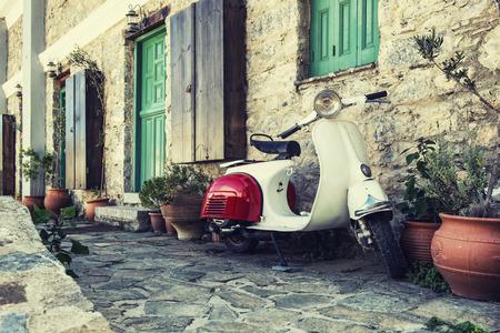Old scooter garé par le mur dans la rue déserte de Karpathos, Grèce. Poster traitée avec filtre vintage.