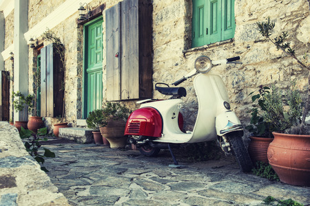 Old scooter parked by the wall in the empty street of Karpathos, Greece. Post processed with vintage filter. Archivio Fotografico