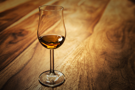 Nosing glass with scotch single malt whisky on the old wooden table