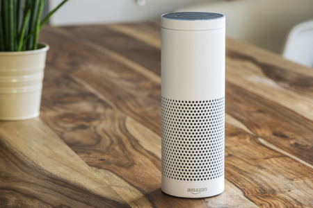 MUENSTER - JANUARY 27, 2018: White Amazon Echo Plus, Alexa Voice Service activated recognition system photographed on wooden table in living room, Packshot showing Amazon Logo Editöryel