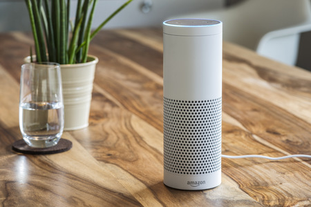 MUENSTER - JANUARY 27, 2018: White Amazon Echo Plus, Alexa Voice Service activated recognition system photographed on wooden table in living room, Packshot showing Amazon Logo 報道画像
