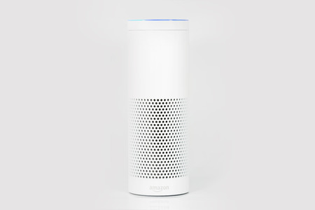 MUENSTER - JANUARY 27, 2018: White Amazon Echo Plus, Alexa Voice Service activated recognition system photographed on white studio backdrop, Packshot showing Amazon Logo Редакционное