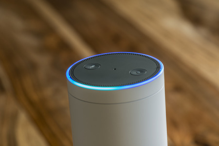 MUENSTER - JANUARY 27, 2018: White Amazon Echo Plus, Alexa Voice Service activated recognition system photographed on wooden table in living room Editoriali