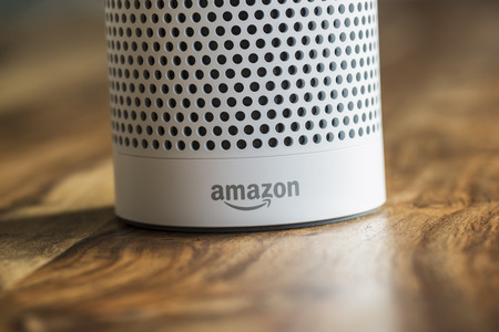 MUENSTER - JANUARY 27, 2018: White Amazon Echo Plus, Alexa Voice Service activated recognition system photographed on wooden table in living room, Packshot showing Amazon Logo Editorial