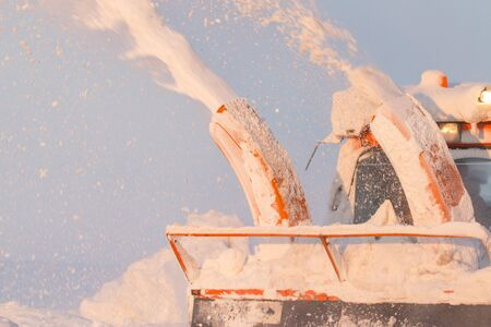 Snow truck cleaning snow from the road and streets working at sunset light on snowy day Stock Photo