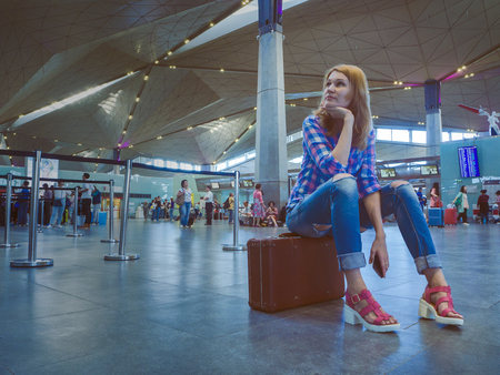 Attractive white woman with a phone in his hand sitting on a suitcase in an airport lounge, and dreams about the rest. Beautiful woman with retro vintage luggage in airport terminal Editorial