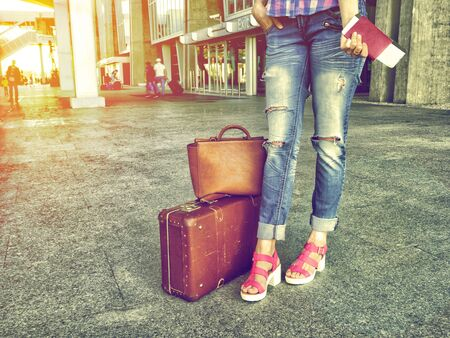 The girl with a passport in hands and plane ticket odizhaet flight for travel with retro luggage. The concept of tourism, holiday, vacation, migration