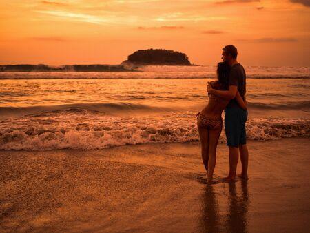 mujer mirando el horizonte: pareja joven y bella en la playa viendo la puesta de sol y el horizonte. Marina. Hermoso el hombre y la mujer cerca del mar al atardecer