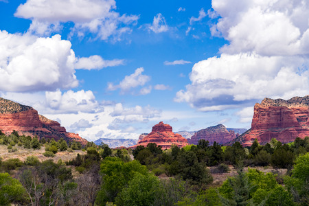 Amazing Red Rock Country near Sedona, Arizona. Displaying colorful sand and limestone rocks and cliffs, with blue sky and white clouds.