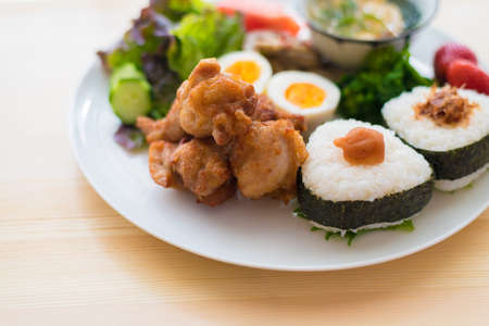 The image of breakfast. Onigiri and fried chicken plate.