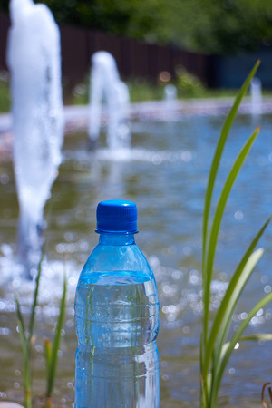 source of water: bottle of drinking water against the source water fountain