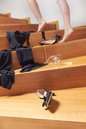 Shoes, dress and an empty glass of wine are on the wooden stairs, girl is in a hurry to her boyfriend for sex.