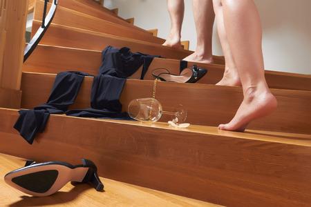 sex: Schoenen, kleding en een leeg glas wijn op de houten trap, meisje is in een haast om haar vriendje voor seks. Stockfoto
