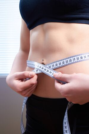 weightless: young girl with a waist measuring volume, abdominal muscles on stomach Stock Photo