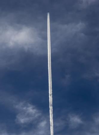 A white airplane trace in the sky Stock Photo