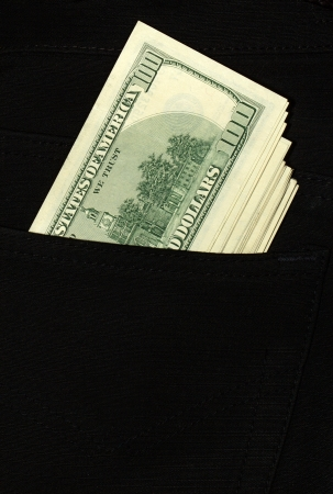 100 dollar bills stick out of the pocket of black jeans photo