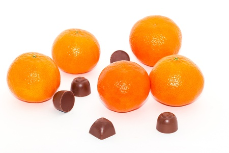 Tangerine and chocolate candies on a white background