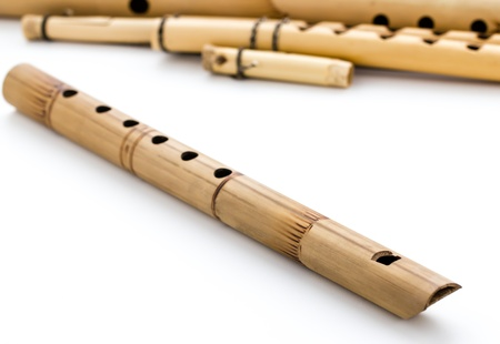 Wooden and bamboo flutes on a white background photo