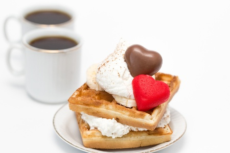 Sweet waffles with whipped cream and chocolate and two cups of coffee.