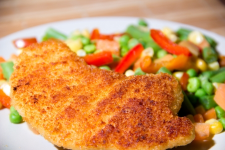 Fried chicken breast with vegetables close up. Stock Photo