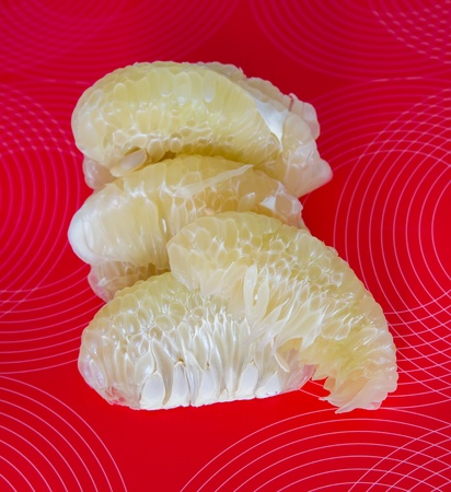 pummelo: Pummelo pealed and cut on slices on the red background.