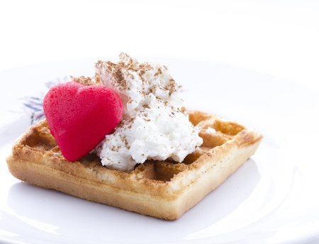 Waffle with sweet cream and red heart shaped marzipan candy.