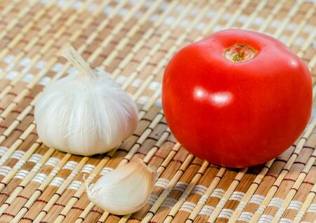 A tomato and garlic on tablecloth close up