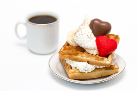 Sweet waffles with whipped cream and chocolate and marzipan candies and a cup of coffee. Stock Photo
