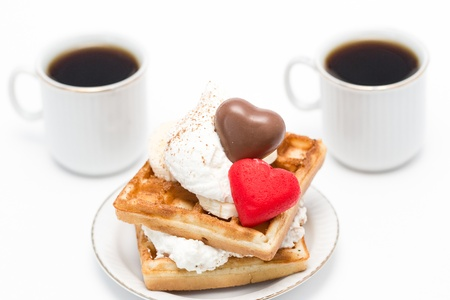 Sweet waffles with whipped cream and chocolate and marzipan candies and two cups of coffee. Stock Photo