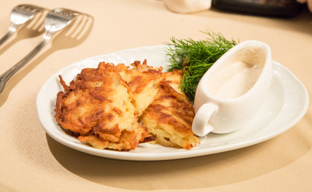 Russian potato cake fried with sour cream sauce. Stock Photo