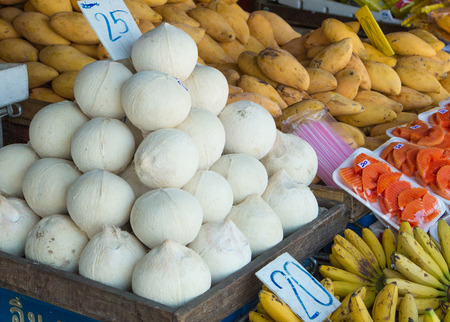 Coconuts and other fruits for sale in Thai market Stock Photo