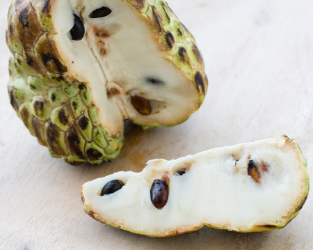 Custard apple with a cut slice on the light background