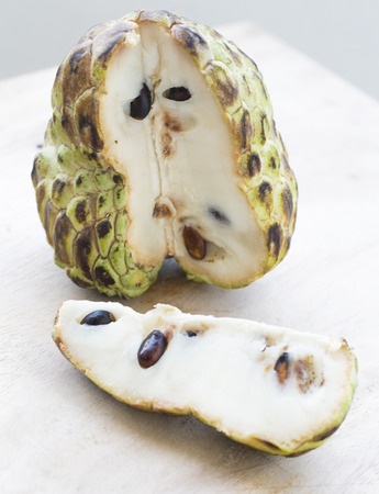 Custard apple (anona) with a cut slice on the light background