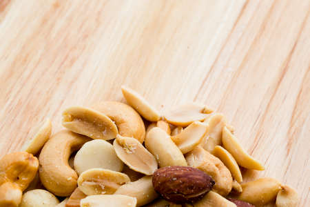 Wooden background with salted mixed nuts at the bottom Stock Photo