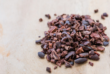 Processed cocoa nibs on the wooden surface